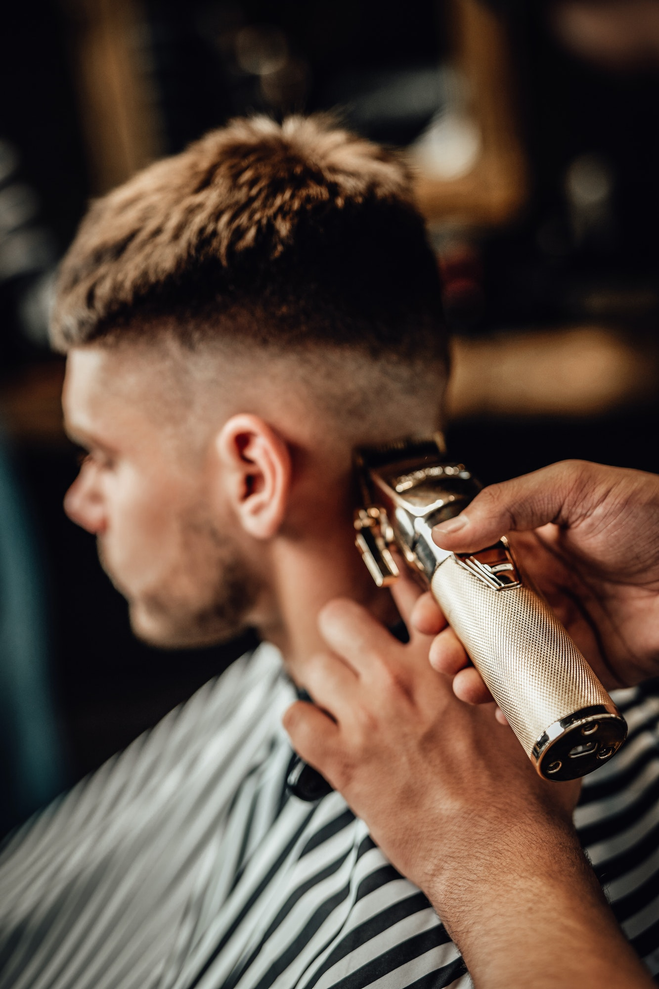 barber-cutting-guy-s-hars-with-silver-clipper-in-saloon.jpg